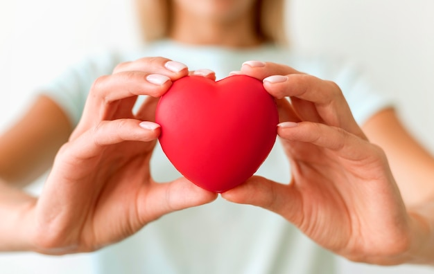 Defocused woman holding heart shape
