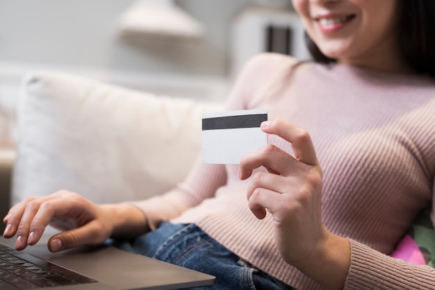 Defocused woman holding up credit card