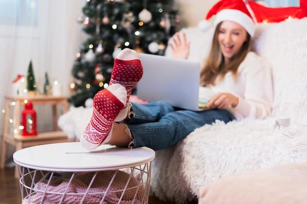 노트북에 화상 통화 채팅을하는 빨간 양말에 defocused 여자, 집에서 크리스마스 시간을 즐기십시오
