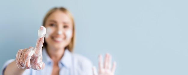 Расфокусированные женщина моет руки и лицо