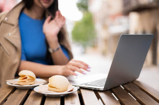 Defocused woman working on laptop outside while having lunch