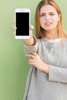 카메라를 향해 휴대 전화 화면을 보여주는 defocused 젊은 여자