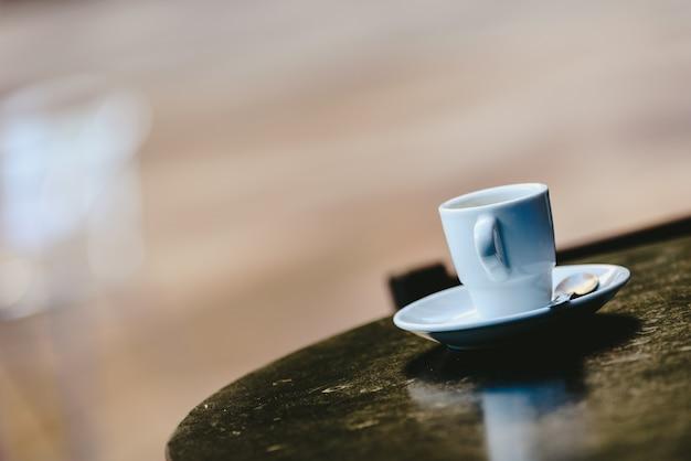 Белая кофейная чашка с defocused предпосылкой и открытым космосом для текста.