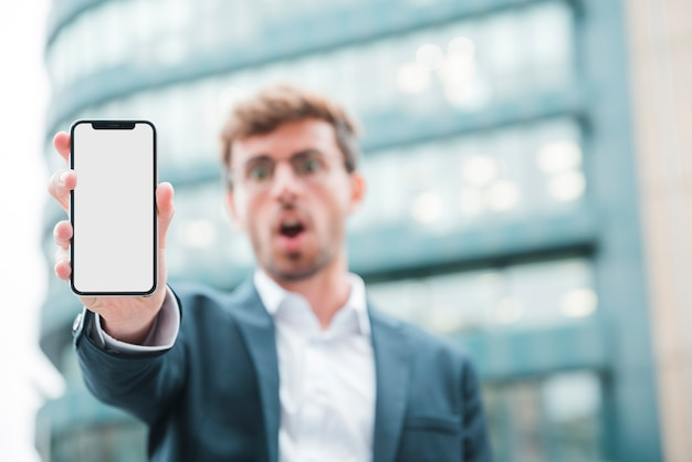 Defocussed young businessman showing mobile phone
