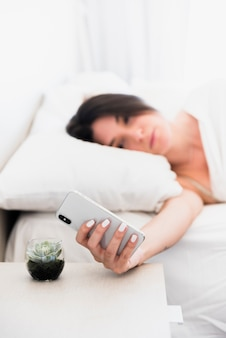 Defocussed young woman lying on bed looking at smartphone