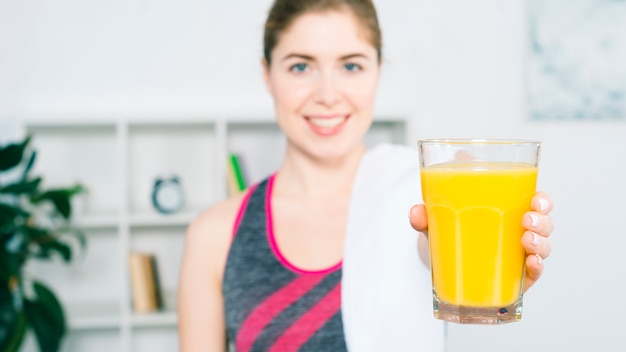ジュースのグラスを提供してデフォーカス若い女性