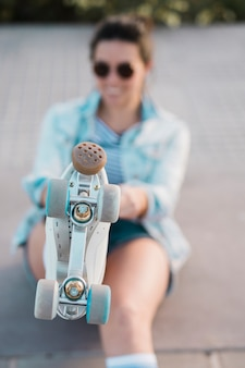 Defocussed young woman showing foot with roller skate
