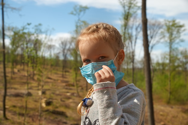 Deforestation. ecological problems of the planet, quarantine. little girl in a medical mask at a deforestation site