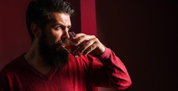 デグステーション、テイスティング。ウイスキーのガラスを持つひげを生やした男。ブランデーやコニャックを飲む男性。高価な飲み物。