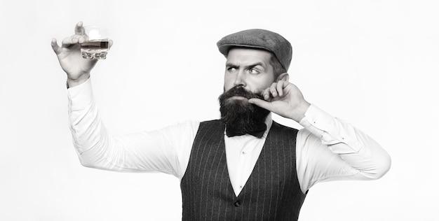 Дегустатор. мужчина с бородой держит стакан бренди. концепция дегустации и дегустации. бородатый бизнесмен в элегантном костюме с бокалом виски. сомелье пробует дорогой напиток.