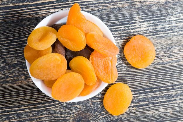 乾燥した熟したアプリコット、オレンジ、伝統的な、丸い白いガラスプレートのドライフルーツの甘さが便利