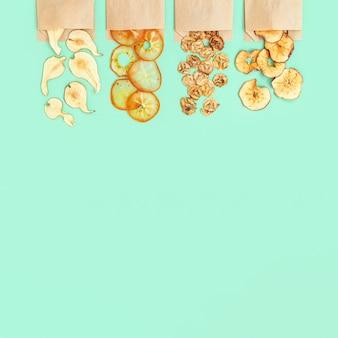 リンゴ、バナナ、柿、梨のドライフルーツチップスを紙のパッケージに入れて