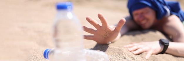 Обезвоженный человек ползет по песку за бутылкой питьевой воды крупным планом
