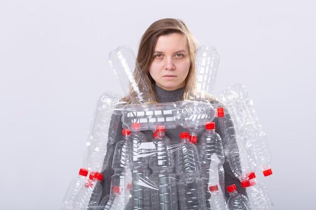 탈수 된 아픈 여자는 플라스틱 병에 드레스와 함께 서 있습니다. 환경 오염 문제