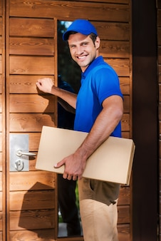 집으로 배달. 주거 집 문을 두드리는 동안 골판지 상자를 들고 웃는 젊은 택배