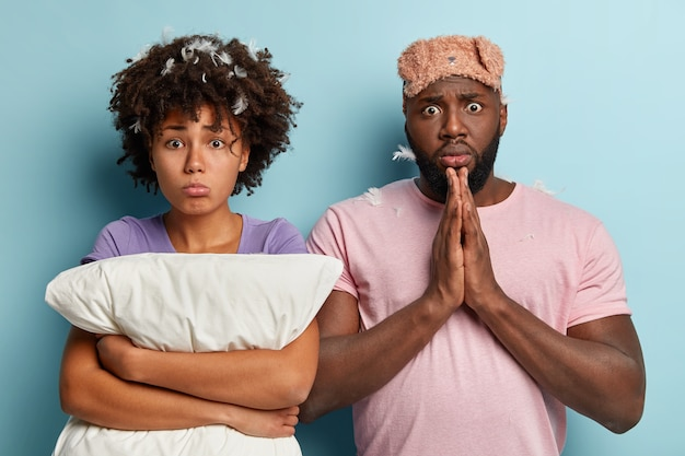 Dejected black woman with afro haircut, embraces white pillow, shocked black man keeps palms together, has bugged eyes, wears sleepmask, stands closely to each other. sleeping and rest concept