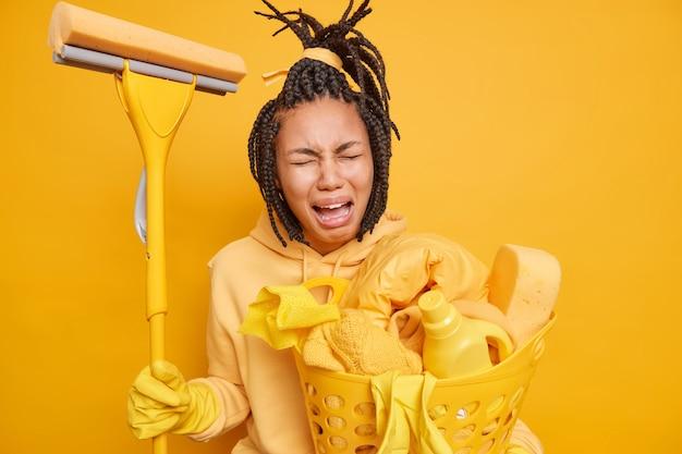 La donna depressa dalla pelle scura con i dreadlocks piange dalla stanchezza tiene la scopa e il cesto della biancheria laundry