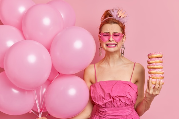Dejected displeased redhead young female cries from despair holds pile of delicious doughnuts and bunch of helium balloons feels unhappy