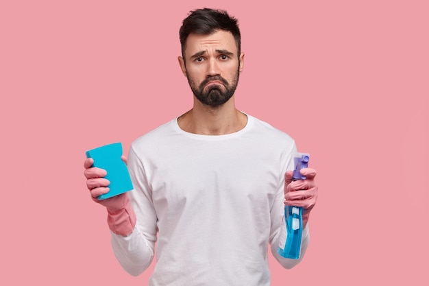 Dejected gloomy man with dark stubble, frowns face in displeasure, holds washing spray and sponge, cleans room alone, has fatigue look
