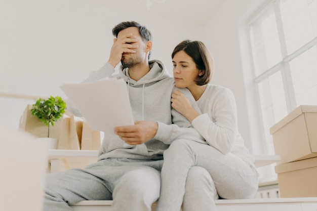 Dejected husband and wife manage finances, receive bill, face financial problem, have gloomy expressions, sit together in empty room, big window behind, cardboard boxes with personal stuff near