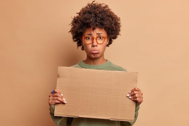 낙심 한 슬픈 여자가 입술을 꽉 쥐고 정면에서 불행하게 보이며 광고 콘텐츠에 대한 빈 골판지를 보유하고 베이지 색 벽 위에 절연 광학 안경을 착용