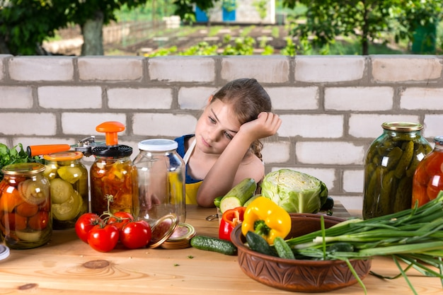 新鮮な野菜やガラスの瓶の大規模な品揃えを見つめている彼女の頭を手に持って屋外のテーブルに座って野菜を瓶詰めする落胆した少女
