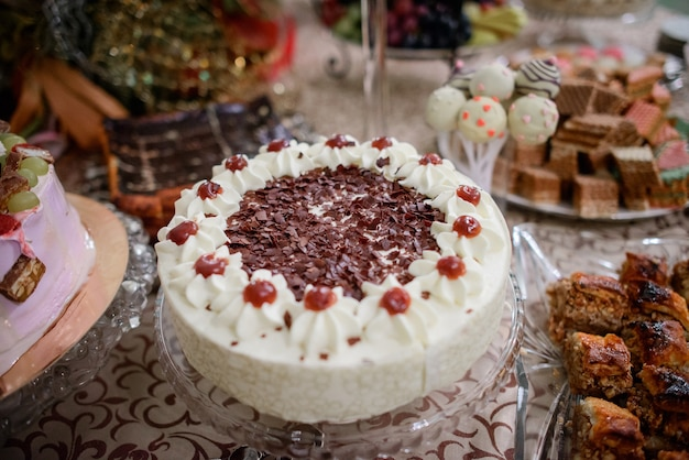 Delcious cake with cream and cherries stands on glass plate
