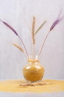Вкусная желтая вермишель с вазой с пшеницей