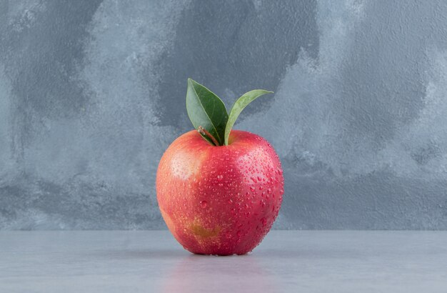 A delectable apple displayed on marble .