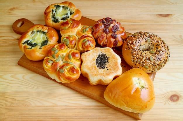Восхитительный сладкий и соленый хлеб ассорти на деревянном подносе, который подается на деревянном столе