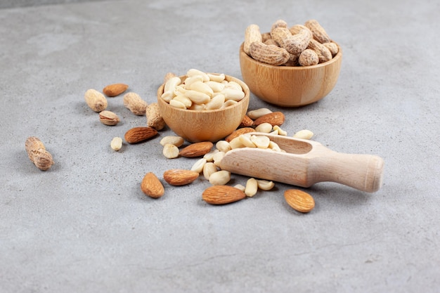 A delectable assortment of nuts in bowls and scattered next to scoop on marble surface