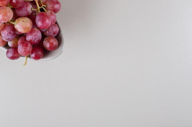 Un delizioso grappolo di uva rossa su marmo