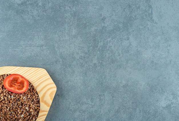 Восхитительно приготовленная гречка на деревянной тарелке, украшенная ломтиками помидоров, на мраморном фоне. фото высокого качества