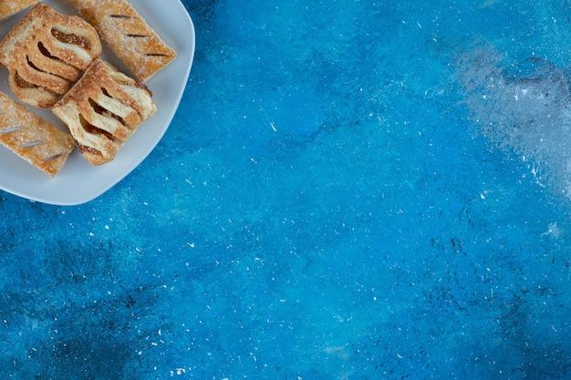 파란색 배경에 접시에 잼과 함께 즐거운 쿠키. 고품질 사진
