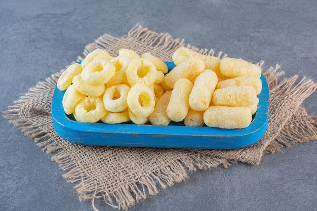 Deliziosi anelli di mais e bastoncini di mais su un piatto di legno sulla trama, sulla superficie di marmo.