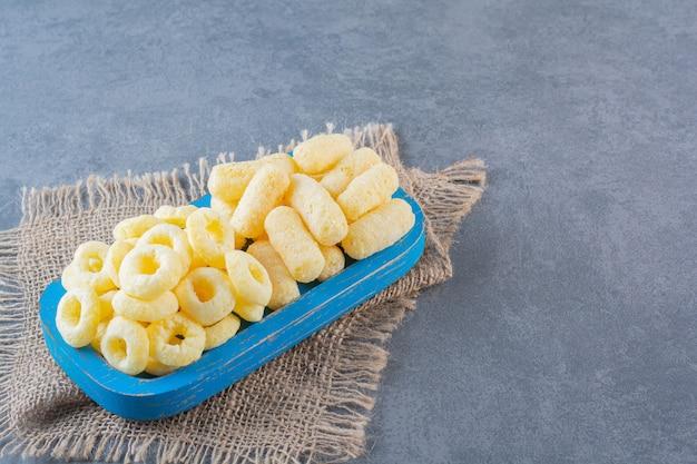 Восхитительные кукурузные кольца на деревянной тарелке на текстуре, на мраморной поверхности.