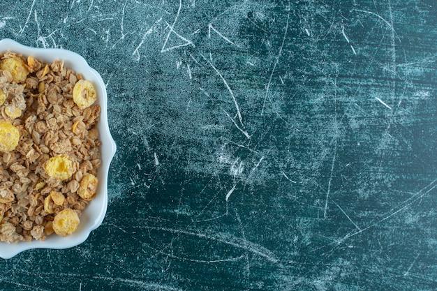 Восхитительные кукурузные хлопья в миске на синем фоне. фото высокого качества