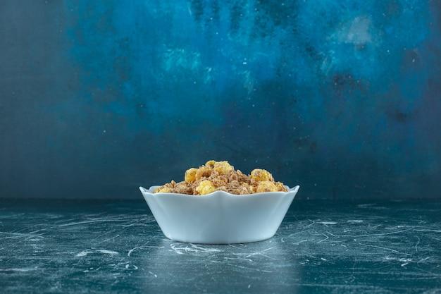 青いテーブルの上にあるボウルの中のおいしいコーンフレーク。