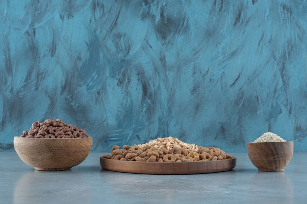 Восхитительные кукурузные хлопья в деревянных мисках на синем столе.