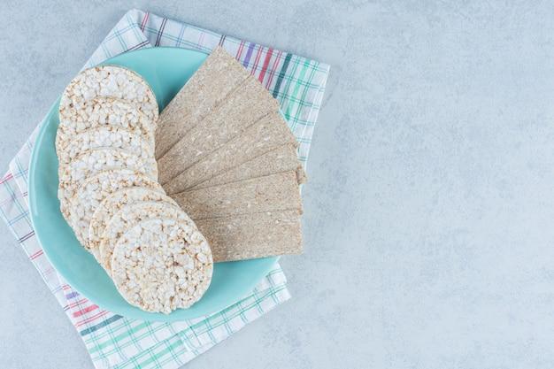Восхитительные хлебцы в тарелке на башне по мрамору.