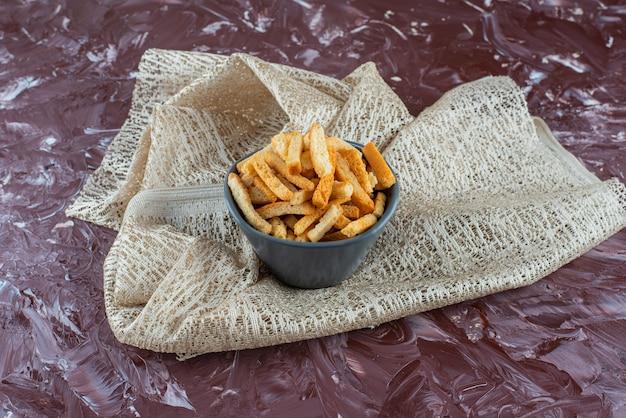 대리석 테이블에 식탁보에 그릇에 맛있는 바삭한 빵 부스러기.