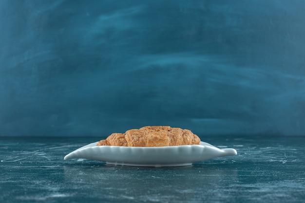파란색 배경에 접시에 맛있는 크루아상. 고품질 사진