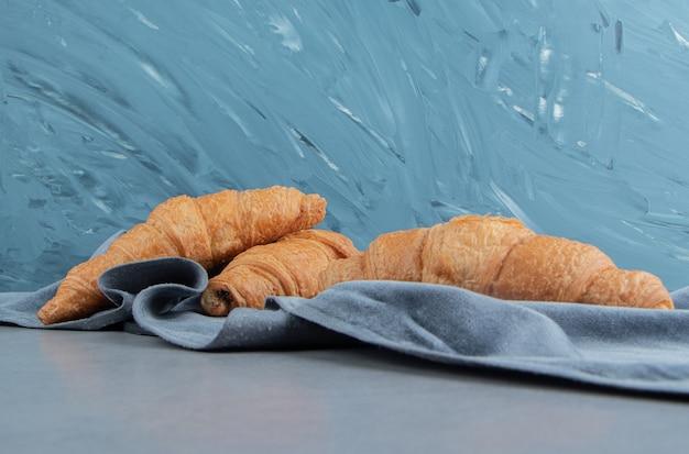 青の背景に、タオルの上においしいクロワッサン。高品質の写真