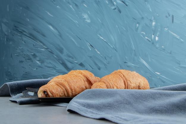 Delizioso croissant su asciugamano, su sfondo blu. foto di alta qualità