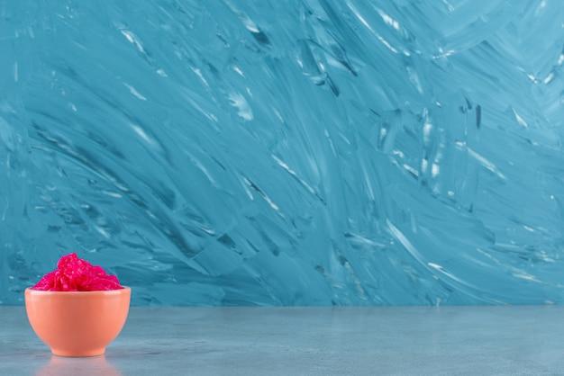 맛있는 발효된 붉은 양배추가 파란 탁자 위에 있는 그릇에 놓여 있습니다.
