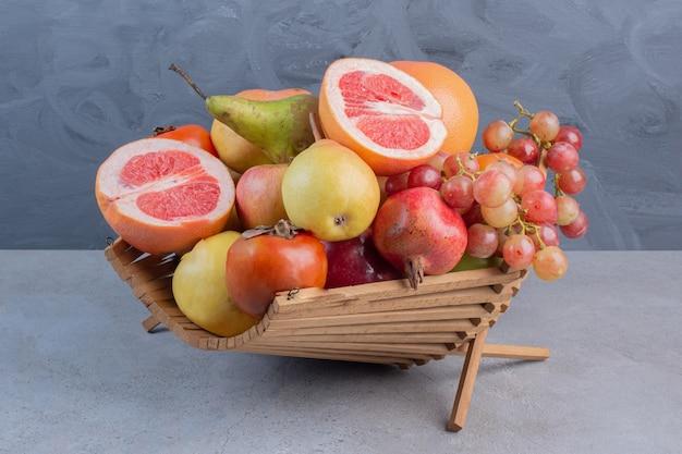 Un delizioso assortimento di frutta in un cesto di legno su sfondo di marmo.