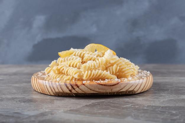 Восхитительная паста фузилли с ломтиками лимона на деревянной тарелке, на мраморной поверхности.