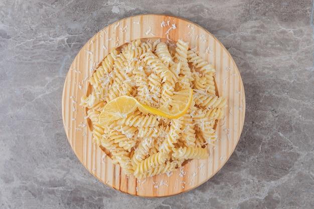 Восхитительная паста фузилли с ломтиками лимона на деревянной тарелке, на мраморе.