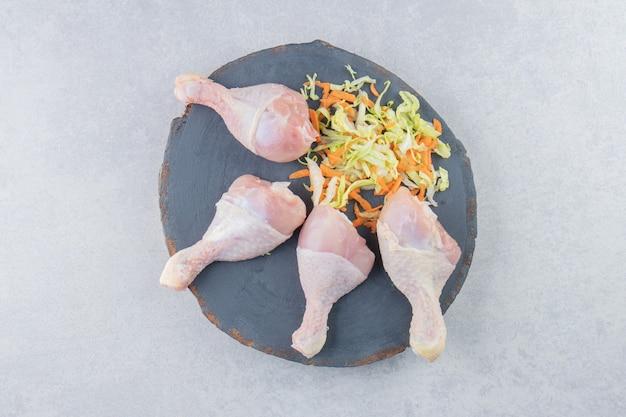 보드의 흰색 표면에 맛있는 채소와 닭 다리