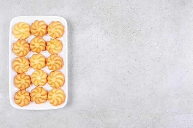 Deliziosi biscotti fatti in casa disposti su un piatto su sfondo marmo.